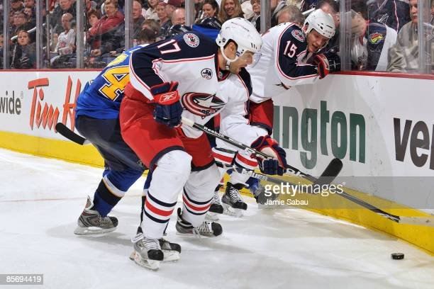 Andrew Murray and Derek Dorsett both of the Columbus Blue Jackets attempt to keep TJ Oshie of the St Louis Blues from gaining control of a loose puck...