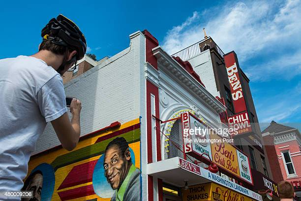 Andrew Nazdin of Northwest DC stops on his bike to photograph progress on a mural being painted Monday August 27 2012 in Washington The mural on the...