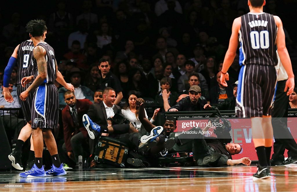 Andrew Nicholson (C) of the Orlando Magic falls into videographers along the end line during an NBA basketball game against the Brooklyn Nets at the Barclays Center in the Brooklyn borough of New York City on April 15, 2015.