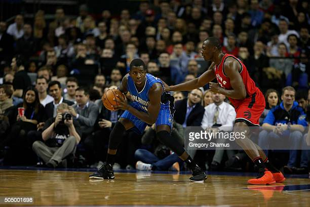 Andrew Nicholson of the Orlando Magic passes against Bismack Biyombo of the Toronto Raptors as part of the 2016 Global Games London on January 14...
