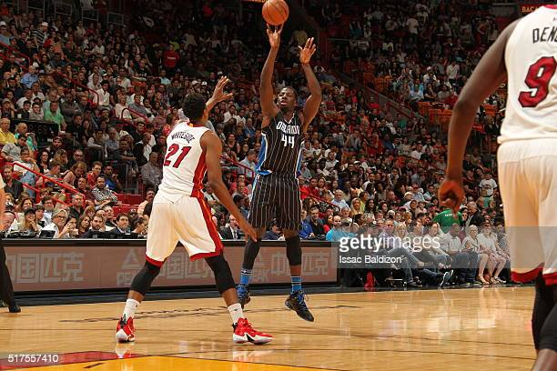 Andrew Nicholson of the Orlando Magic shoots against Hassan Whiteside of the Miami Heat on March 25 2016 at AmericanAirlines Arena in Miami Florida...