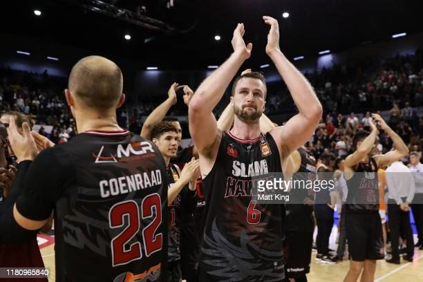 Andrew Ogilvy of the Hawks celebrates victory with team mates after the round two NBL match between the Illawarra Hawks and the Cairns Taipans at...