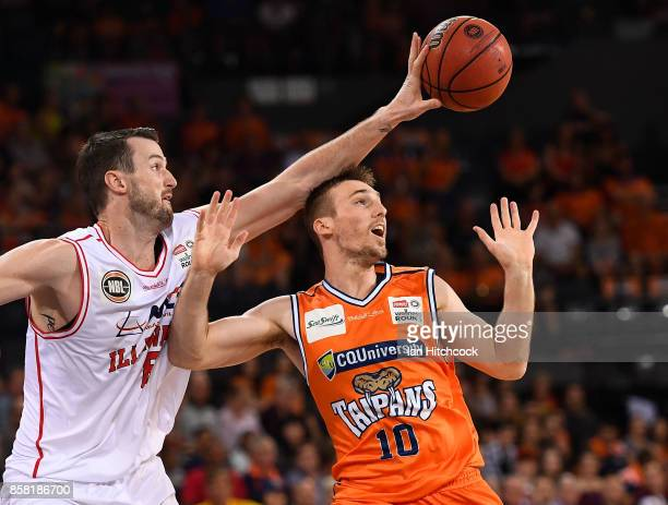 Andrew Ogilvy of the Hawks knocks the ball away from Mitch McCarron of the Taipans during the round one NBL match between the Cairns Taipans and the...