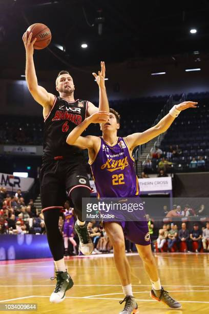 Andrew Ogilvy of the Hawks lays up a shot under pressure from Dane Pineau of the Kings during the NBL preseason match between the Illawarra Hawks and...