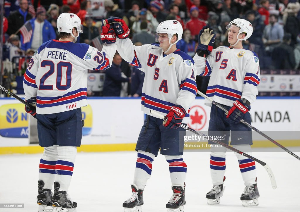 Andrew Peeke #20 of United States high fives Casey Mittelstadt #11 of United States with Brady Tkachuk #7 waiting to join in the celebration following the third period of play in the Quarterfinal IIHF World Junior Championship game at the KeyBank Center on January 2, 2018 in Buffalo, New York.
