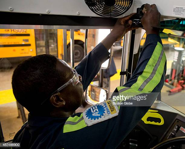 Andrew Prince a technician with the Boston Public Schools installing the new video camera system in a Boston Public School Bus at the Readville Bus...