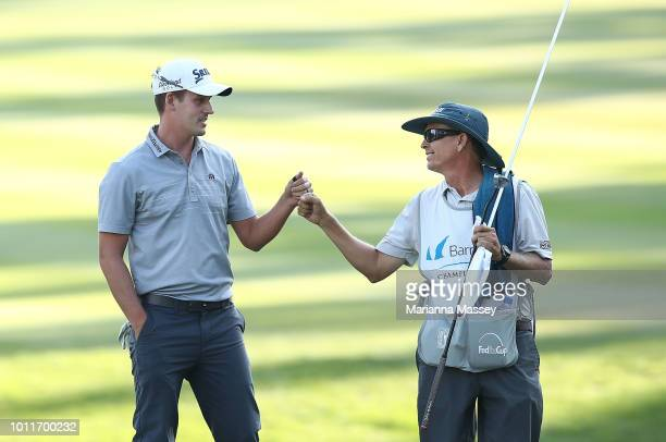 Andrew Putnam celebrates with his caddie after putting in for birdie on the 18th hole during the final round of the Barracuda Championship at...
