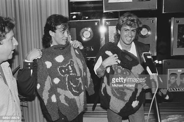 Andrew Ridgeley and George Michael of Wham holding koala motif sweaters during the pop duo's 1985 world tour January 1985 Behind them are awards for...
