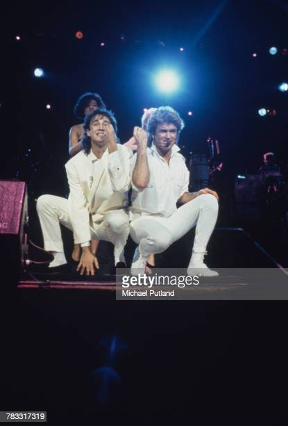 Andrew Ridgeley and George Michael of Wham! performing during the pop duo's 1985 world tour in January 1985. In the background are backing singers...
