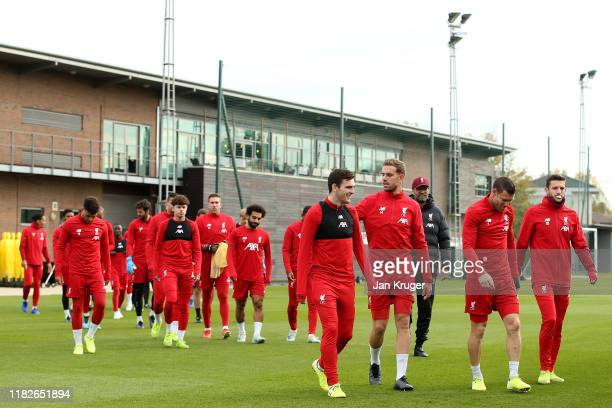 Andrew Robertson Jordan Henderson and James Milner lead the team out during a Liverpool training session ahead of the Champions League group E match...