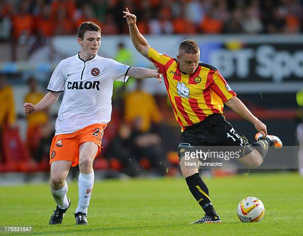 Andrew Robertson of Dundee United tries to stop John Baird of Partick Thistle long range shot during the Scottish Premiership League match between...