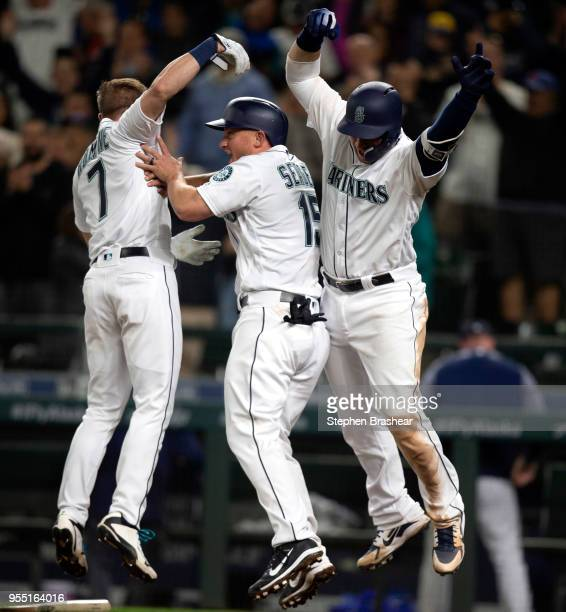 Andrew Romine Kyle Seager and Mike Zunino celebrate after Seager scored the winning run on a single by Ryon Healy of the Seattle Mariners off of...