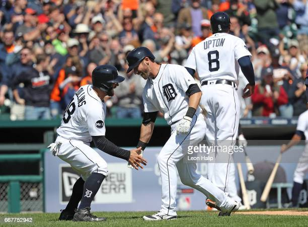 Andrew Romine of the Detroit Tigers celebrates with teammate Tyler Collins after hitting a fourth inning grand slam during the game against the...