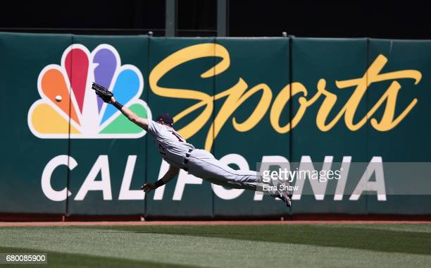 Andrew Romine of the Detroit Tigers dives but can not catch a ball hit by Adam Rosales of the Oakland Athletics in the third inning at Oakland...