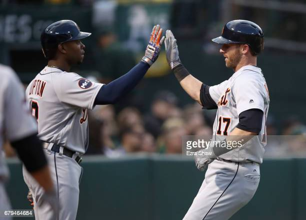 Andrew Romine of the Detroit Tigers is congratulated by Justin Upton after he scored on a hit by Victor Martinez in the third inning against the...