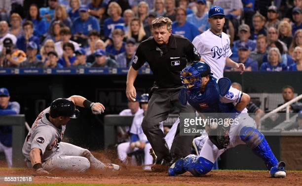 Andrew Romine of the Detroit Tigers slides into home as he scores past Drew Butera of the Kansas City Royals in the fifth inning at Kauffman Stadium...