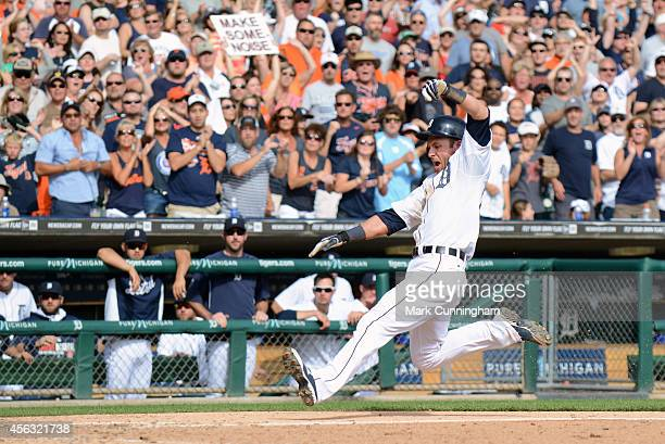 Andrew Romine of the Detroit Tigers slides safely into home plate in the 8th inning of the game against the Minnesota Twins at Comerica Park on...
