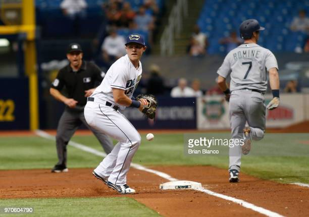 Andrew Romine of the Seattle Mariners reaches first base ahead of first baseman Jake Bauers of the Tampa Bay Rays off of a throwing error by...
