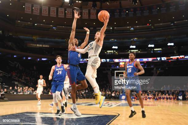Andrew Rowsey of the Marquette Golden Eagles drives to the basket past Brandon Cyrus of the DePaul Blue Demons the first round of the Big East Men's...