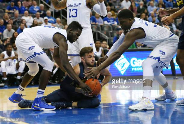 Andrew Rowsey of the Marquette Golden Eagles in action against Ismael Sanogo and Desi Rodriguez of the Seton Hall Pirates during a game at Prudential...