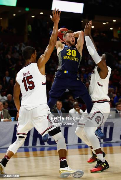 Andrew Rowsey of the Marquette Golden Eagles passes against PJ Dozier and Duane Notice of the South Carolina Gamecocks in the first half during the...