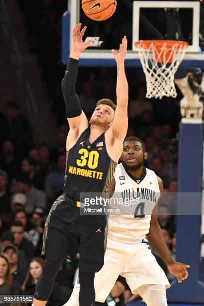 Andrew Rowsey of the Marquette Golden Eagles pulls down a rebound Eric Paschall of the Villanova Wildcats during the quarterfinal round the Big East...
