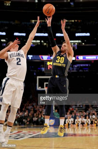 Andrew Rowsey of the Marquette Golden Eagles takes a shot as Collin Gillespie of the Villanova Wildcats defends during quarterfinals of the Big East...