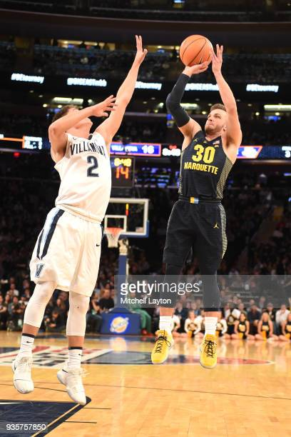 Andrew Rowsey of the Marquette Golden Eagles takes a shot over Collin Gillespie of the Villanova Wildcats during the quarterfinal round the Big East...