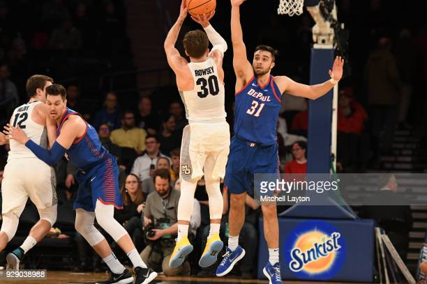 Andrew Rowsey of the Marquette Golden Eagles takes a shot over Max Strus of the DePaul Blue Demons the first round of the Big East Men's Basketball...