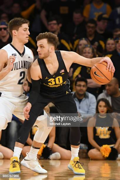 Andrew Rowsey of the Marquette Golden Eagles tries to dribble around Collin Gillespie of the Villanova Wildcats during the quarterfinal round the Big...