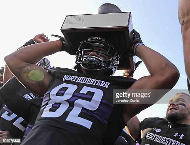 Andrew Scanlan of the Northwestern Wildcats holds the 'Land of Lincoln' trophy over his head after a win against the Illinois Fighting Illini at Ryan...