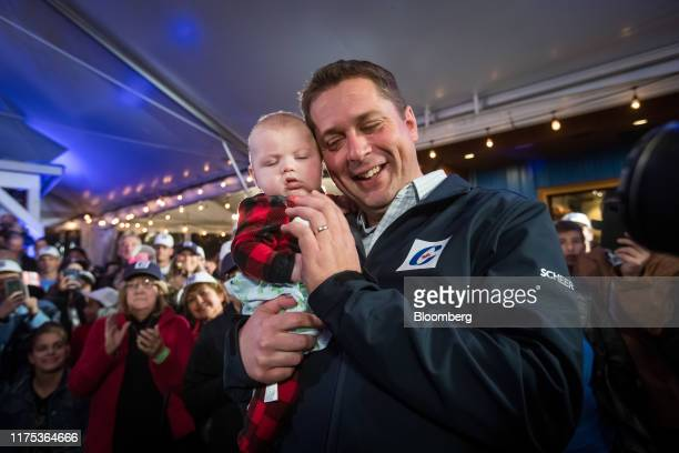 Andrew Scheer leader of Canada's Conservative Party right holds a baby during a rally in Langley British Columbia Canada on Friday Oct 11 2019 Scheer...