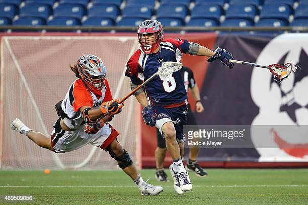 Andrew Sellers of the Boston Cannons looks for a shot on goal with pressure from Ken Clausen of the Denver Outlaws at Gillette Stadium on April 12...