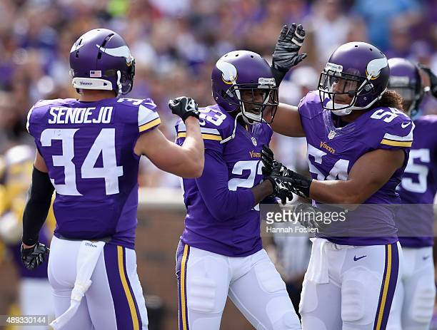 Andrew Sendejo and Eric Kendricks of the Minnesota Vikings congratulate teammate Terence Newman on a tackle against the Detroit Lions during the...