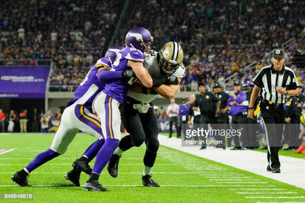 Andrew Sendejo and Harrison Smith of the Minnesota Vikings push Coby Fleener of the New Orleans Saints out of bounds during the game on September 11...