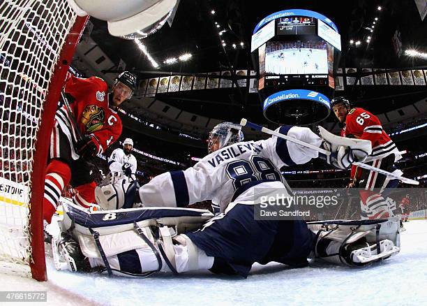 Andrew Shaw and Jonathan Toews of the Chicago Blackhawks watch as goaltender Andrei Vasilevskiy of the Tampa Bay Lightning makes a save during the...