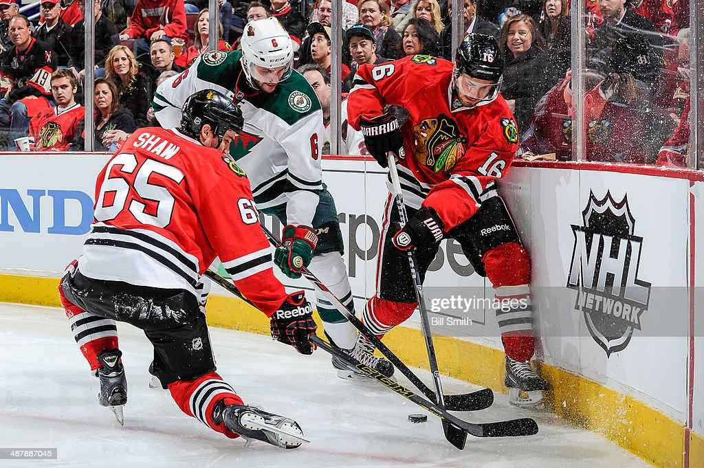 Andrew Shaw #65 and Marcus Kruger #16 of the Chicago Blackhawks battle for the puck against Marco Scandella #6 of the Minnesota Wild in Game One of the Second Round of the 2014 Stanley Cup Playoffs at the United Center on May 02, 2014 in Chicago, Illinois.