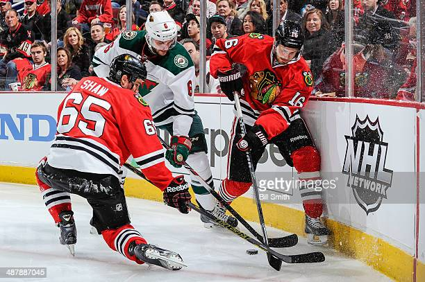 Andrew Shaw and Marcus Kruger of the Chicago Blackhawks battle for the puck against Marco Scandella of the Minnesota Wild in Game One of the Second...
