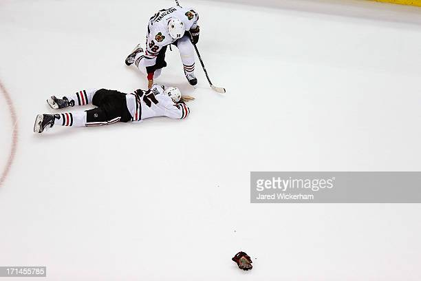 Andrew Shaw lies on the ice while being tended to by teammate Michal Rozsival of the Chicago Blackhawks following a play in the first period against...