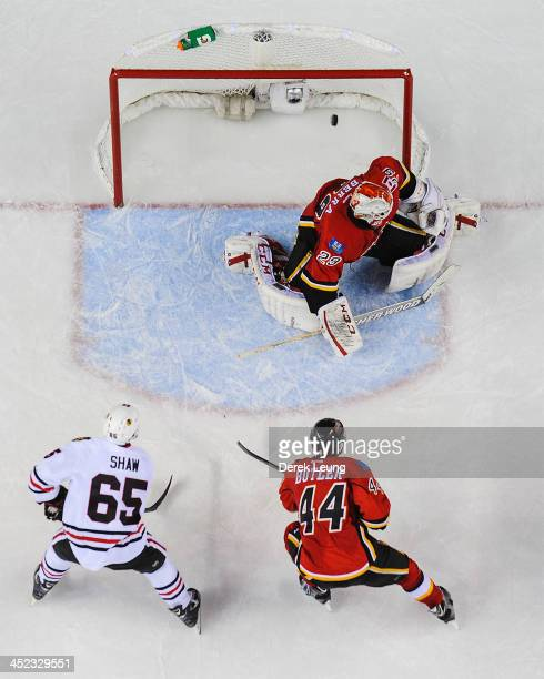 Andrew Shaw of the Chicago Blackhawks and Chris Butler of the Calgary Flames watch the gamewinning shot by Patrick Kane fly past Reto Berra during an...