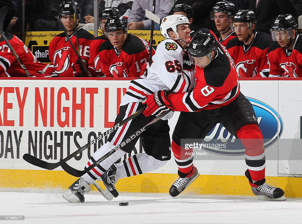 Andrew Shaw #65 of the Chicago Blackhawks and Dainius Zubrus #8 of the New Jersey Devils battle for a loose puck during the game at the Prudential Center on March 27, 2012 in Newark, New Jersey.