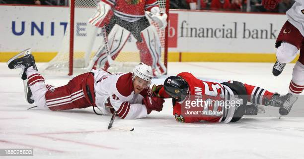 Andrew Shaw of the Chicago Blackhawks and Jeff Halpern of the Phoenix Coyotes hit the ice after colliding at the United Center on November 14 2013 in...