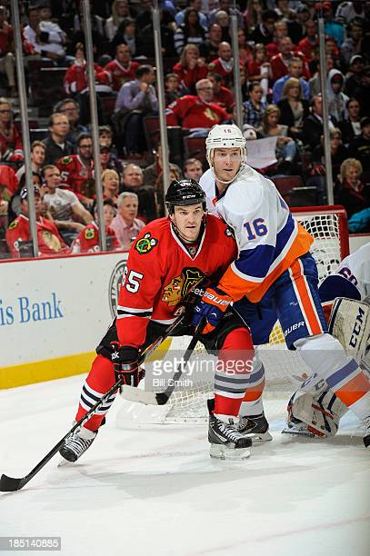 Andrew Shaw of the Chicago Blackhawks and Peter Regin of the New York Islanders watch for the puck during the NHL game on October 11, 2013 at the...