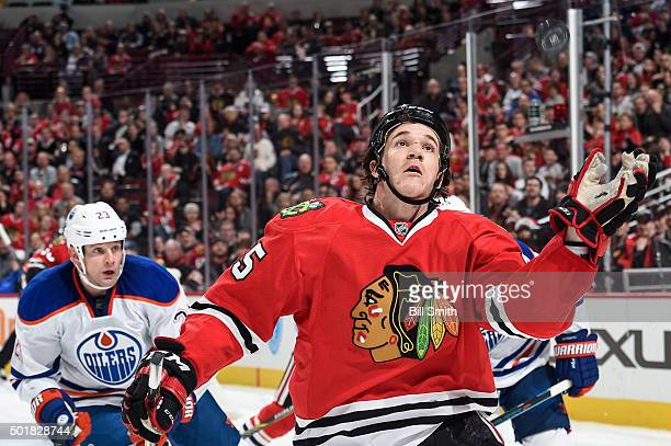 Andrew Shaw of the Chicago Blackhawks attempts to catch the puck as Matt Hendricks of the Edmonton Oilers watches from behind in the second period of...
