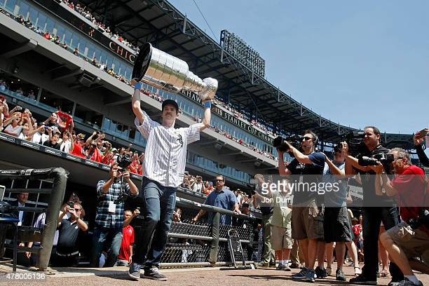 Andrew Shaw of the Chicago Blackhawks carries the Stanley Cup onto the field before the game between the Chicago White Sox and the Texas Rangers at...
