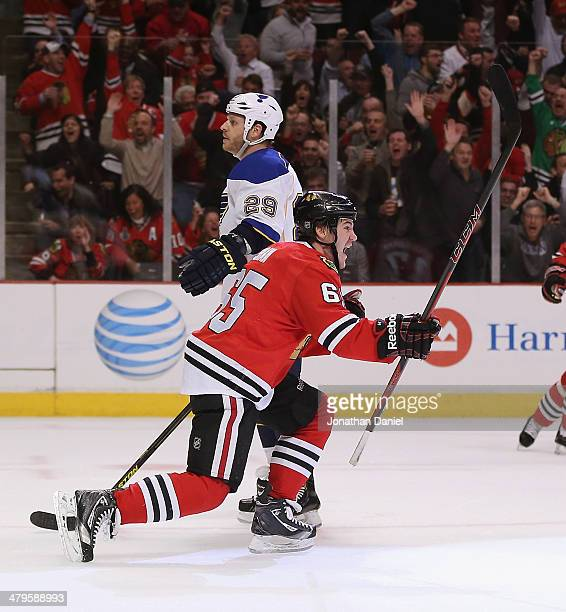 Andrew Shaw of the Chicago Blackhawks celebrates a second period goal as he skates past Steve Ott of the St Louis Blues at the United Center on March...
