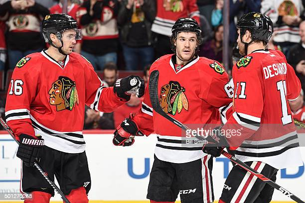 Andrew Shaw of the Chicago Blackhawks celebrates with Marcus Kruger and Andrew Desjardins after scoring against the Vancouver Canucks in the third...