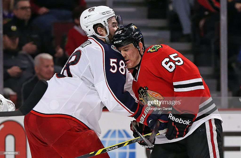 Andrew Shaw #65 of the Chicago Blackhawks collides with David Savard #58 of the Columbus Blue Jackets at the United Center on March 27, 2015 in Chicago, Illinois. The Blue Jackets defeated the Blackhawks 5-2.