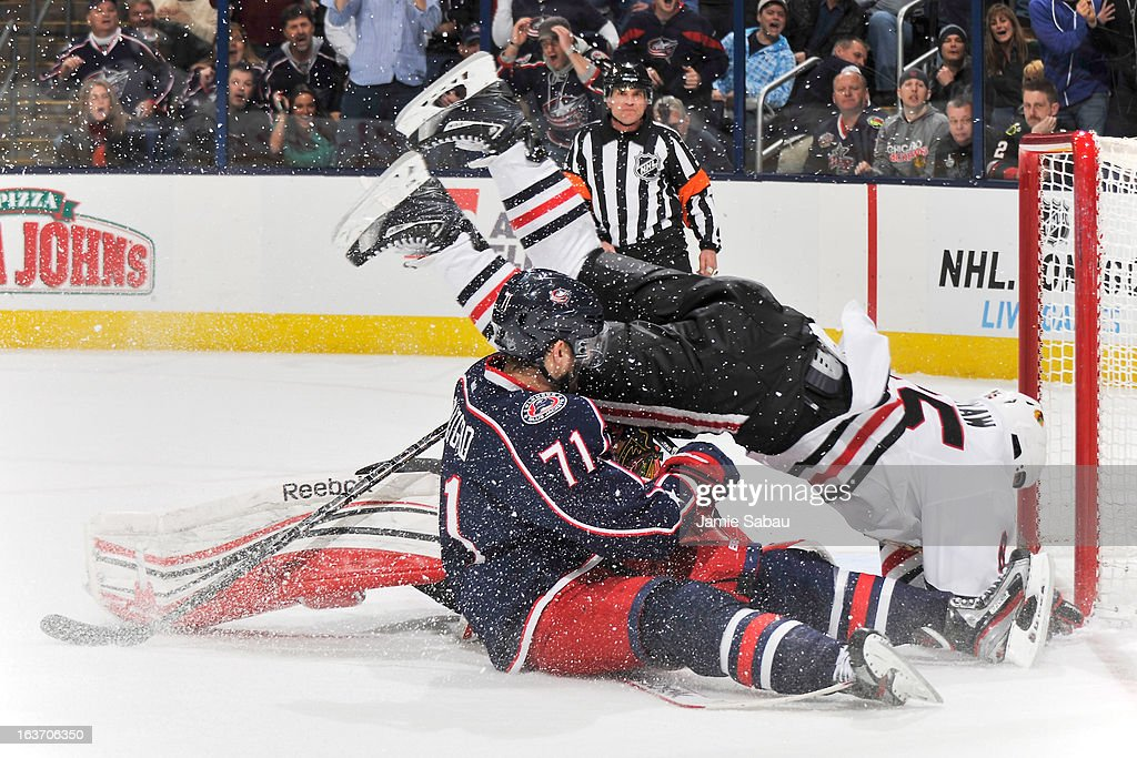 Andrew Shaw #65 of the Chicago Blackhawks falls over goaltender Corey Crawford #50 of the Chicago Blackhawks and Nick Foligno #71 of the Columbus Blue Jackets during the third period on March 14, 2013 at Nationwide Arena in Columbus, Ohio. Chicago defeated Columbus 2-1 in a shootout.