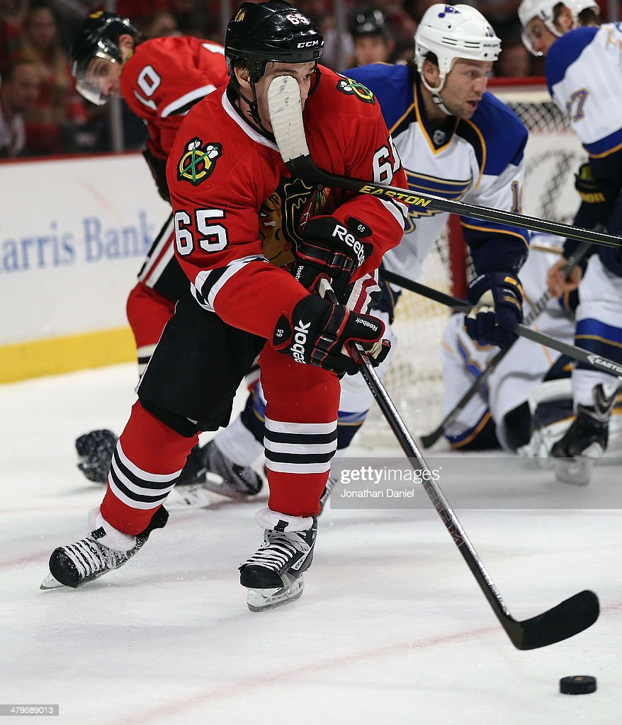 Andrew Shaw #65 of the Chicago Blackhawks gets a stick in his face as he controls the puck against the St. Louis Blues at the United Center on March 19, 2014 in Chicago, Illinois.